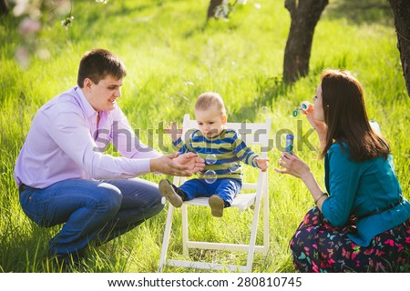 father and mother blowing soap bubbles. family playing outside. happy child with parents in park. happy family concept. portrait of happy people. man, woman, boy spending spare time outside together. - stock photo