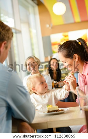Father and mother feeding child cake cafe woman man eating - stock photo