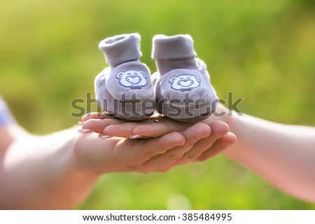 father and mother hold in their hands baby shoes - stock photo