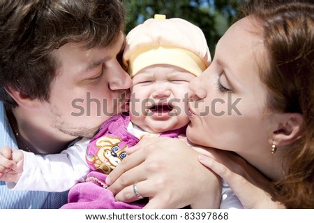 Father and mother kissing a child, the child is crying and sad - stock photo