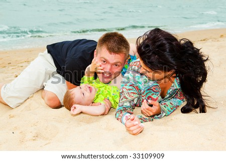 Father and mother playing with baby on the sand