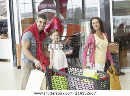 Father and mother push young daughter in shopping trolley through mall - stock photo