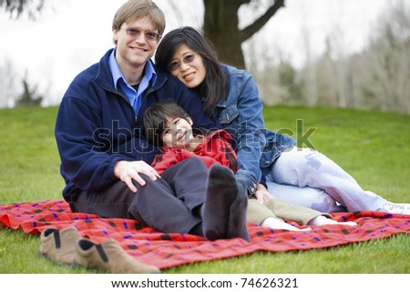 Father and mother sitting at park with disabled son, interracial family - stock photo