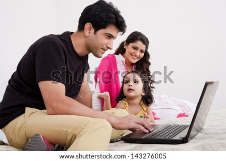 father and mother using laptop with daughter, Muslim family of three.