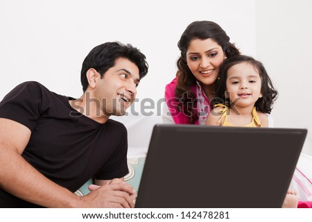 father and mother using laptop with the daughter on bed - stock photo