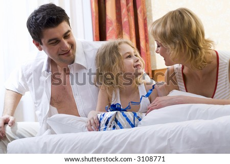 Father and Mother waking their daughter and making her a present on the bed
