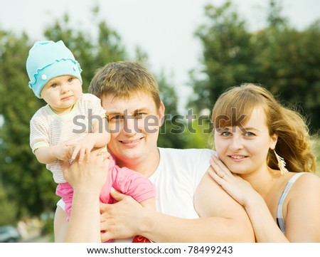 father and mother with baby at the park - stock photo