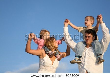 father and mother with the children on the shoulders - stock photo