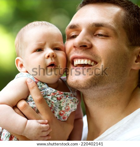 father and newborn daughter playing in the park in love - stock photo