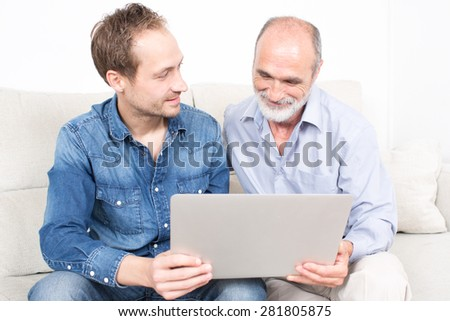 Father and older son looking at laptop - stock photo