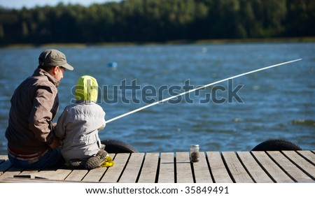 Father and small son fishing together on lake
