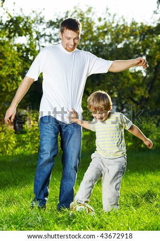 Father and small son play a ball in park - stock photo