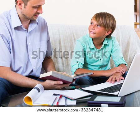 Father and smiling teenager boy studying with laptop indoors - stock photo