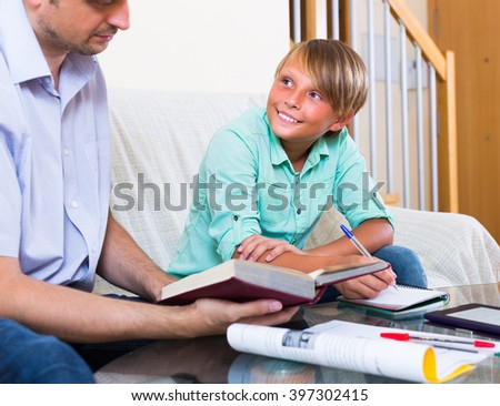 Father and smiling teenager son studying with laptop at home - stock photo