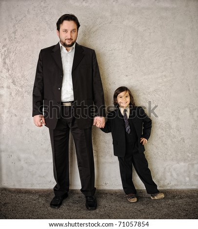 Father and son against wall