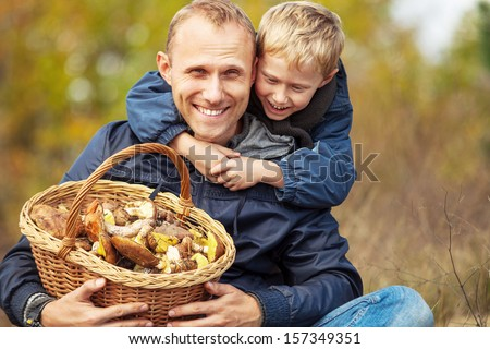 Father and son are happy that they have found a basket full of mushrooms - stock photo