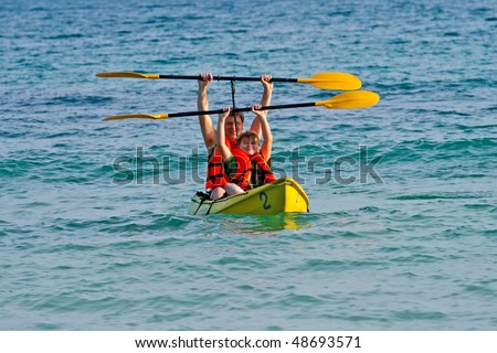 father and son are paddling with a canoe in open sea - stock photo