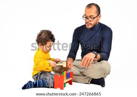 Father and son are playing together as part of the didactic autism children therapy. A therapist is working with little child. Didactic therapeutic toys for autism.   - stock photo
