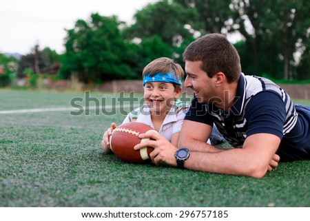 Father and son are resting after a game of American football - stock photo