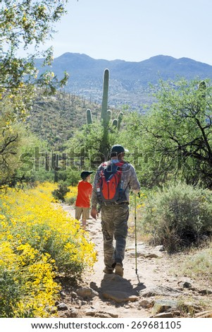 Father and son are traveling on foot through the Sonoran Desert. Saguaro National Park, Arizona, USA - stock photo