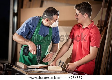 Father and son are working together in a workshop. Mid-adult carpenter is teaching his son to work with him.
