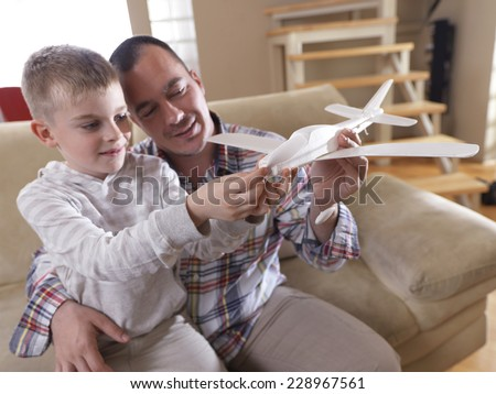 father and son assembling airplane toy at modern home living room indoor - stock photo