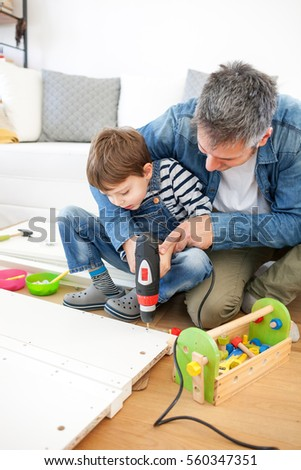 Delightful Father And Son Assembling Furniture At Home
