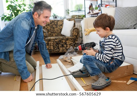 Wonderful Father And Son Assembling Furniture At Home
