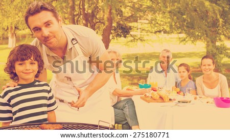 Father and son at barbecue grill with extended family having lunch in the park - stock photo