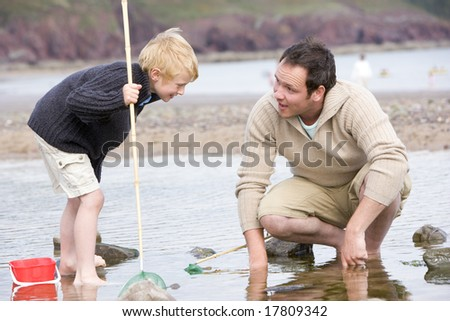 Father and son at beach fishing - stock photo