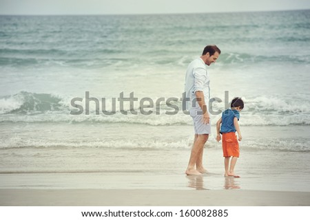 Father and son at beach holding hands looking at the ocean together on vacation - stock photo