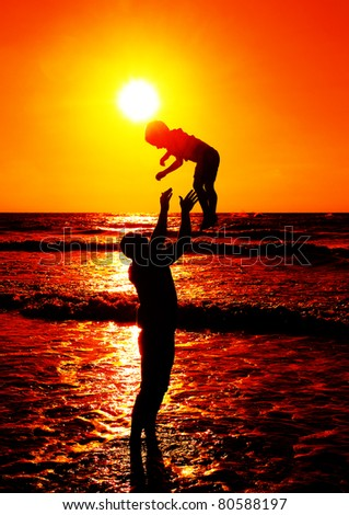 father and son at sea watching sunset - stock photo