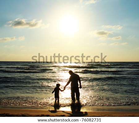 Father and son at sea watching the sunset - stock photo