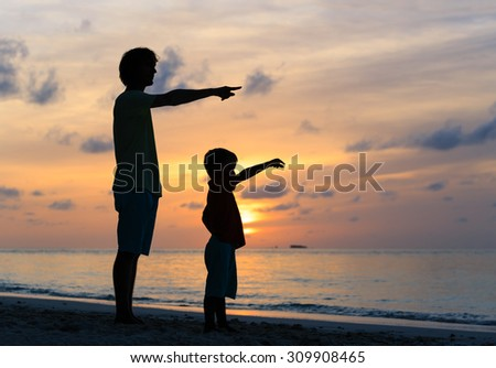 father and son at sunset beach, pointing at the sun