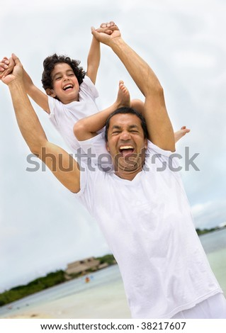 Father and son at the beach having fun - stock photo