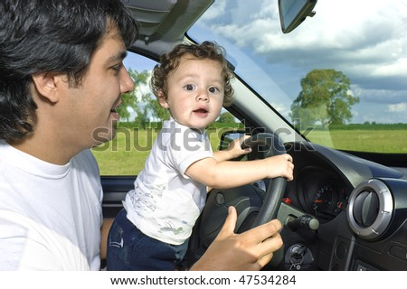 Father and son at the wheel. Learning to drive and having fun. - stock photo