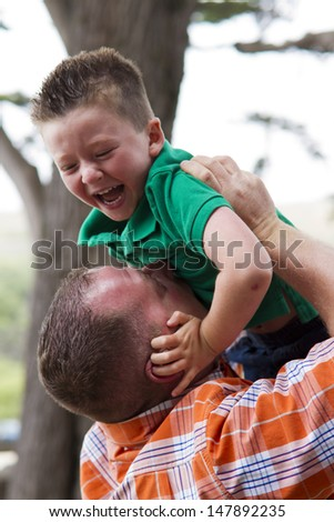 Father and son being playful outdoors together. - stock photo