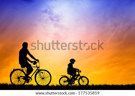 Father and son biking at sunset