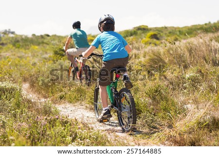 Father and son biking through mountains on a sunny day