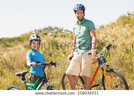 Father and son biking through mountains on a sunny day - stock photo