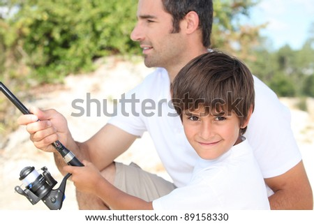 Father and son bonding during fishing trip - stock photo