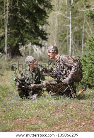 father and son bow hunting together - stock photo