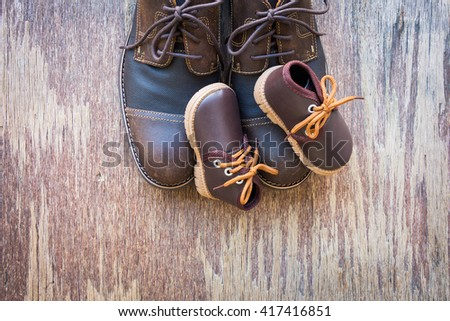 Father and son brown shoes on rustic wooden background, father's day concept - stock photo