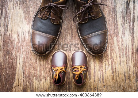 Father and son brown shoes on wooden background, fathers day  - stock photo