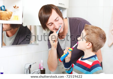 Father and son brushing teeth in bathroom - stock photo