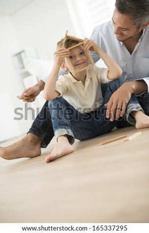 father and son building a small house - stock photo