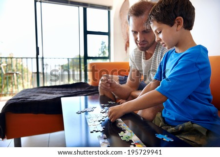 Father and son building puzzles together - stock photo