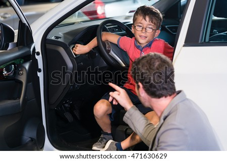 Father and son buying new family car at auto dealership