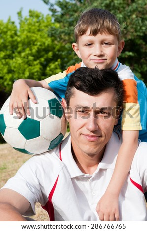 Father and son came to the park to play football and take a picture - stock photo