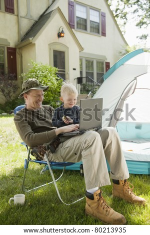 Father and son camping in the front yard with laptop computer - stock photo